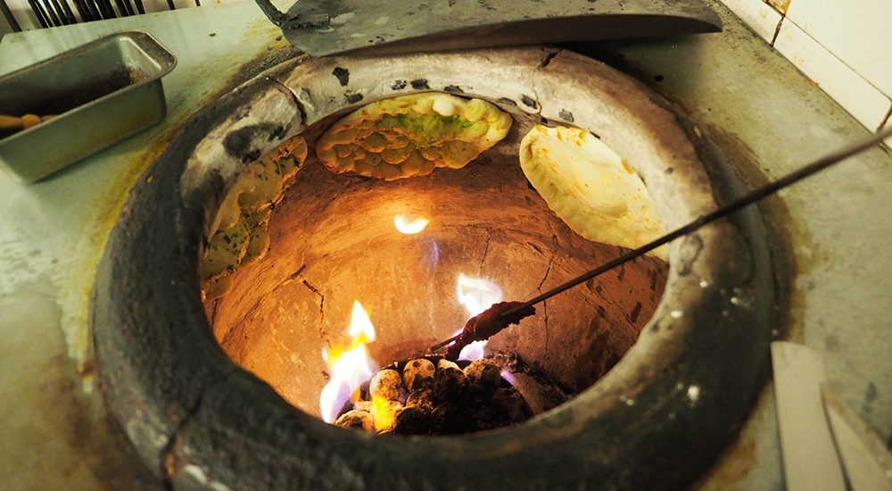 Naan bread cooking in an oven in Little India